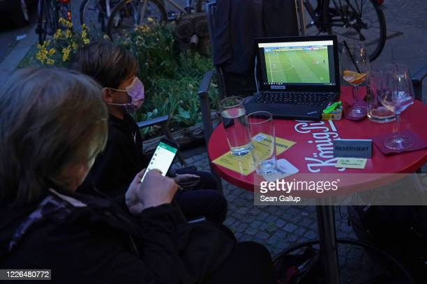 Young fan wearing a protective face mask watches Hertha BSC football club play against Berlin rival 1. FC Union on a laptop computer while sitting...