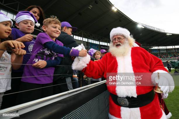 Young fans meet Santa Claus during the Big Bash League match between the Hobart Hurricanes and the Melbourne Renegades at Blundstone Arena on...