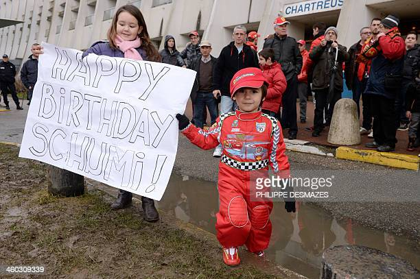 Young fans of German Formula One world champion Michael Schumacher hold a banner reading Happy Birthday Schumi to mark his 45th birthday outside the...