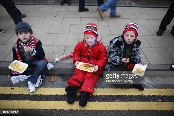 Young fans of non league side Crawley Town enjoy their chips sitting on the kerb in Sir Matt Busby Way outside Old Trafford as their team prepare to...