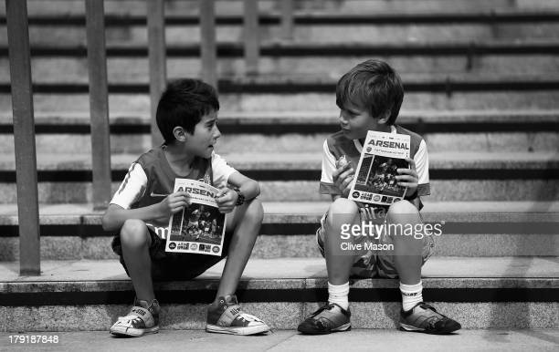 Young fans read their programmes before the Barclays Premier League match between Arsenal and Tottenham Hotspur at Emirates Stadium on September 01...