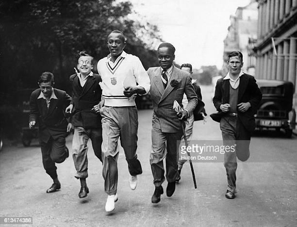 Young fans run along beside the American Olympic sprinter Jessie Ownes as he takes his early morning run in London England 1936