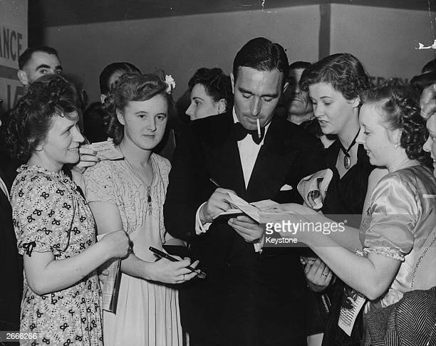 Young fans seek the autograph of England cricketer and journalist Denis Compton during the Denis Compton Ball held at the Empress Hall