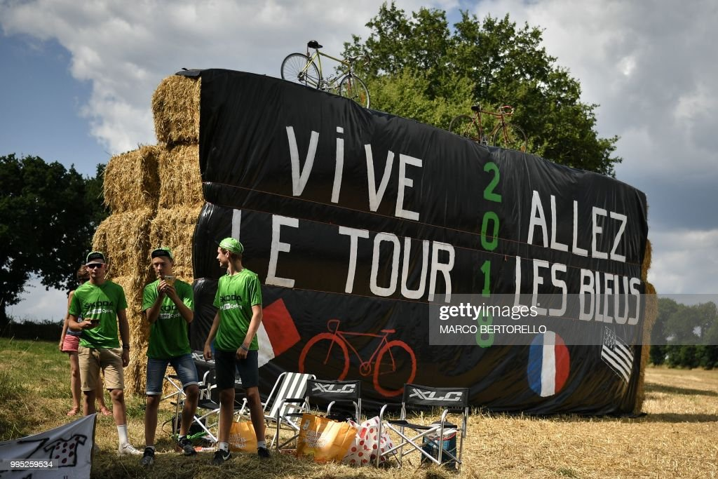 TOPSHOT - Young fans stand by haystacks with banners reading 'Long live the Tour' (L) and 'Go the Blu Ones', referring to the French football team later competing against Belgium in the World Cup semifinal in Russia, during the fourth stage of the 105th edition of the Tour de France cycling race between La Baule and Sarzeau, western France, on July 10, 2018.