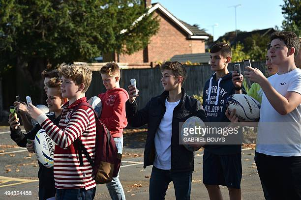 Young fans take pictures as the New Zealand rugby team bus leaves Weybridge west of London on October 26 during the 2015 Rugby World Cup New Zealand...