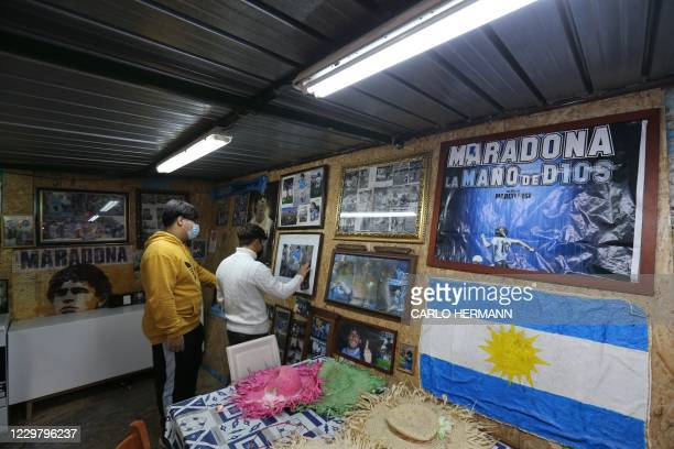 Young fans visit a small spontaneous museum dedicated to Argentinian football legend Diego Maradona on November 26, 2020 in the Spanish quarters of...