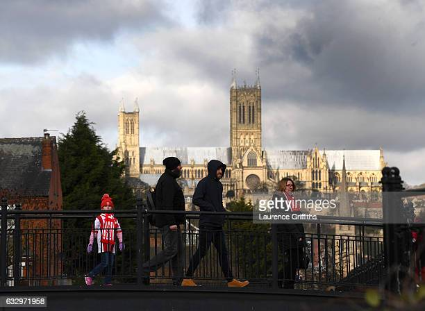 A young fans walks to the stadium in front of Lincoln Cathedral ahead of the Emirates FA Cup Fourth Round match between Lincoln City and Brighton and...