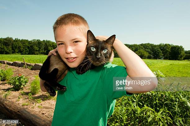 young farm boy with a cat - siamese cat stock pictures, royalty-free photos & images