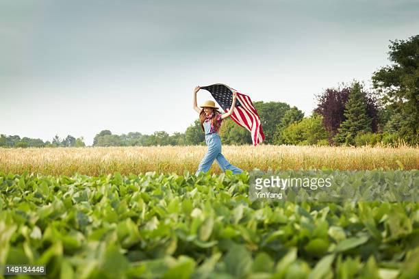 若い女性の農場を走るフィールドに、アメリカの旗