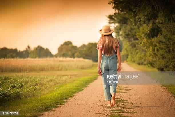 Young explotación Chica caminando en la carretera de campo del campo
