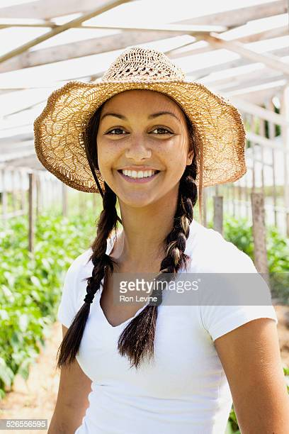 Young farm worker in straw hat, smiling