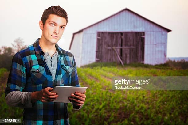 Jeune agriculteur extérieur portrait au coucher du soleil près de Grange avec tablette