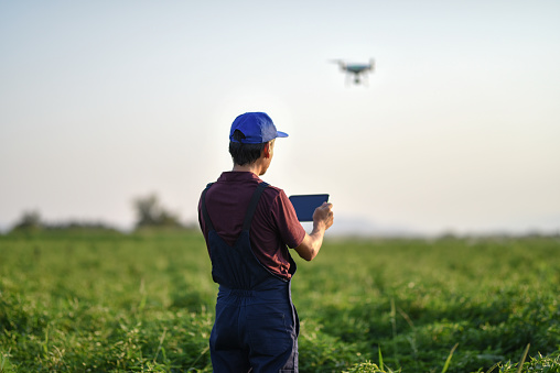 Young farmer flying a drone over a field - gettyimageskorea
