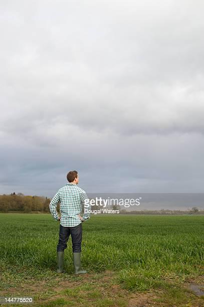Young farmer looking across fields.