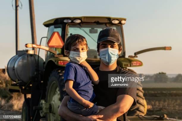 giovane agricoltore in posa con il figlio, entrambi con maschere protettive per il viso - scena rurale foto e immagini stock