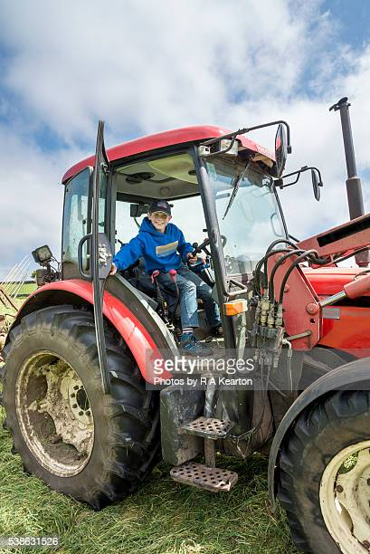 Young farmer sat in a big red tractor
