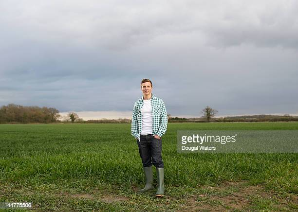 young farmer standing at edge of field. - standing stock pictures, royalty-free photos & images