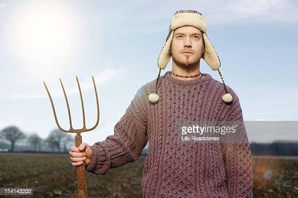 young farmer standing in field - fur hat stock pictures, royalty-free photos & images