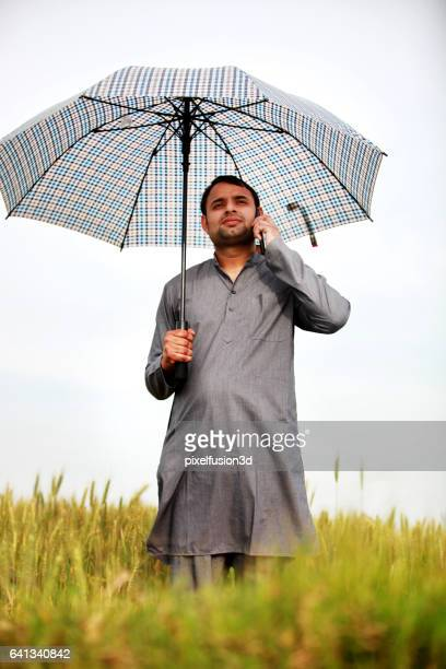 Young farmer standing in green field and talking on mobile phone