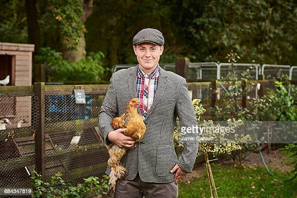 A young farmer stood proudly with a chicken