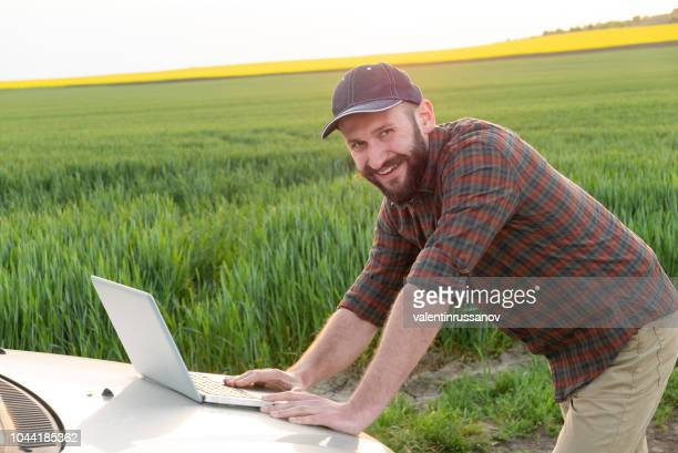 young farmer using laptop in field - agronomist stock pictures, royalty-free photos & images