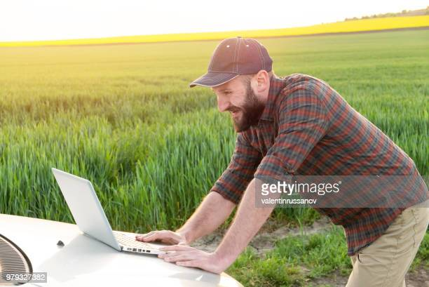 young farmer using laptop on field - agronomist stock pictures, royalty-free photos & images