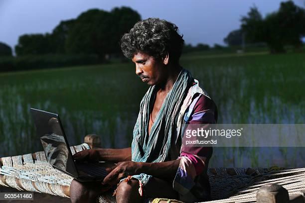 Junger Landwirt mit Laptop