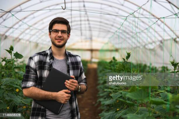 young farmer with laptop is looking at camera - agronomist stock pictures, royalty-free photos & images