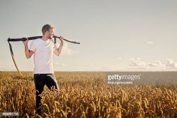 young farmer with scythe - scythe stock photos and pictures