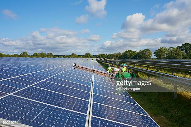 Young farmers cleaning their solar panels