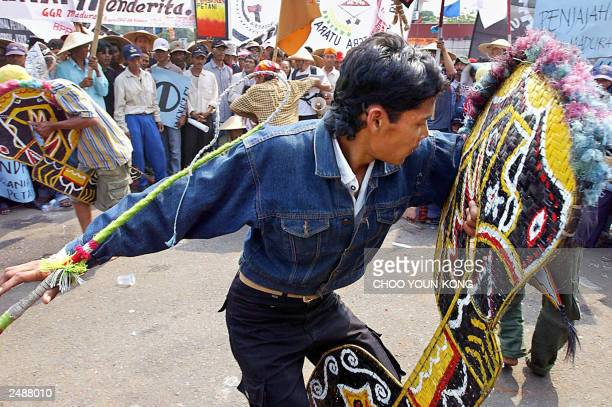 """Young farmers dance to a traditional farmers """"Kuda Lumping"""" to express their anger in front of Parliament in Jakarta 05 August 2003, as hundreds..."""