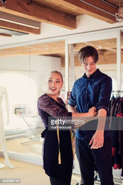 """young fashion designer assistant adjusting clothing on male model. - """"martine doucet"""" or martinedoucet stock pictures, royalty-free photos & images"""