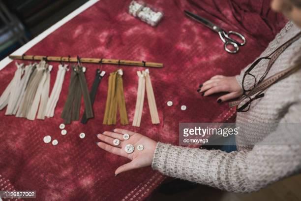 デザイン スタジオのボタンとジッパーを選択する若いファッション ・ デザイナー - 裁縫道具 ストックフォトと画像