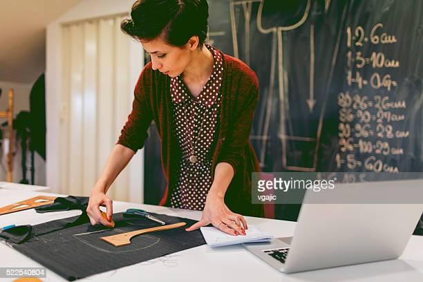 joven diseñadora de moda está trabajando en su taller - montar fotografías e imágenes de stock