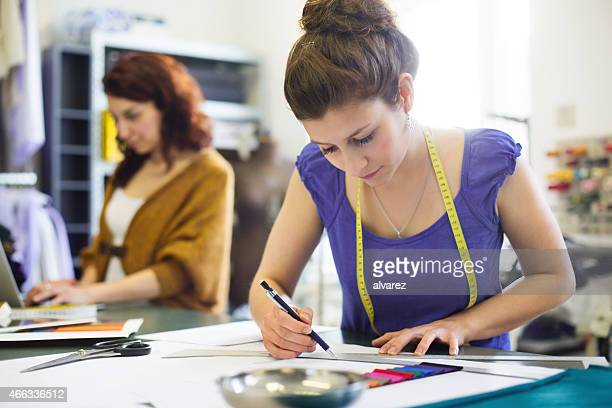 Young fashion designer sketching new dress designs