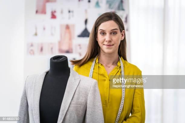 Mode-Designer steht hinter  Stoff an einer Ankleidepuppe