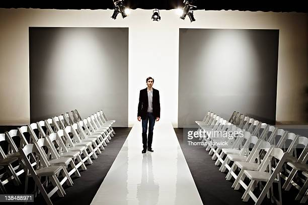 young fashion designer standing on empty catwalk - catwalk stage stock pictures, royalty-free photos & images
