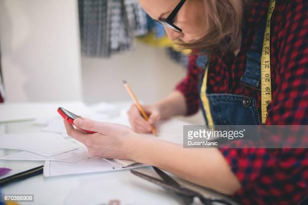 jeune designer de mode conversation sur téléphone portable, je regarde ses créations - tenue d'affaires photos et images de collection