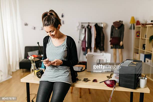 Young fashion designer working in her studio, using smartphone