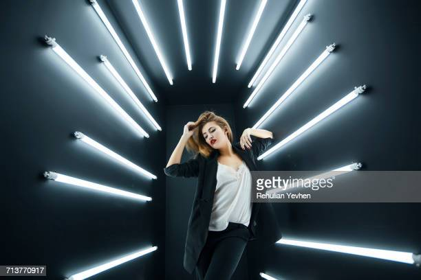 Young fashion model posing in studio, electric lighting behind her