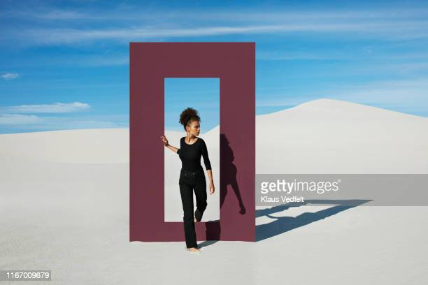 young fashion model walking through door frame at desert - stepping stock pictures, royalty-free photos & images