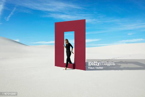young fashion model walking through red door frame at desert against sky - moda fotografías e imágenes de stock