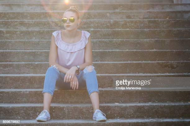 young fashionable beautiful woman sitting on stairs and posing - pink pants stock pictures, royalty-free photos & images