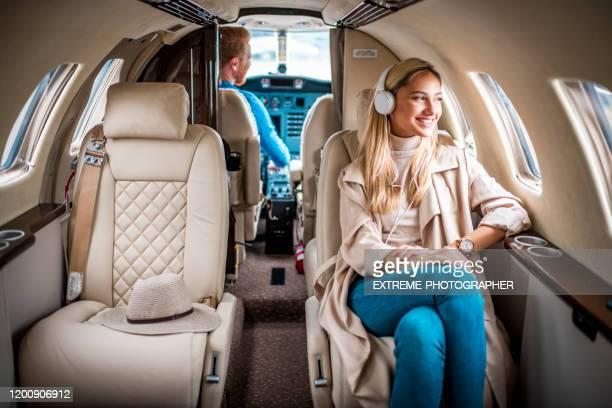 jonge, modieuze blonde vrouw genieten van muziek over de koptelefoon tijdens het vliegen aan boord van een prive-jet - voertuiginterieur stockfoto's en -beelden