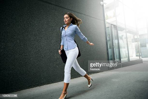 young fashionable business woman with long curly hair running - briefcase stock pictures, royalty-free photos & images