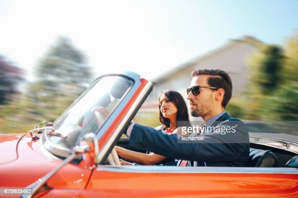 young fashionable couple in an oldtimer convertible sportscar - high society stock pictures, royalty-free photos & images