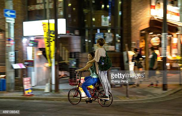Young fashionable Japanese girls ride bicycle on the street at night Amerikamura near Shinsaibashi in the Minami district of Osaka is a vibrant place...