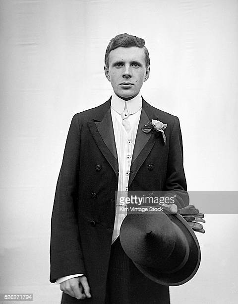 Young fashionable man strikes a pose in his formal tux while holding his top hat and gloves.