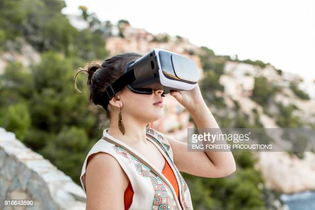 young , fashionable teenager is using virtual reality headset outdoors