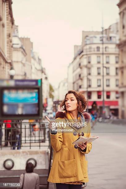 young fashionable tourist searching her way near parisian metro. - paris metro sign stock pictures, royalty-free photos & images